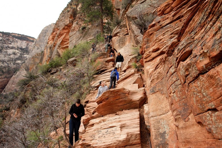 Hikers on their way to Angels Landing in Zion National Park.  In recent years, Zion has taken action to control visitor numbers in order to protect natural resources and the outdoor experience. Across America, in wildlands that have become inundated by mass numbers of people, wildlife values have been diminished. Photo by Alex Proimos
