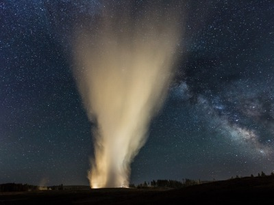 Old Faithful erupts at night beneath the clear constellation of The Milky Way. Photograph by Neil Herbert/NPS