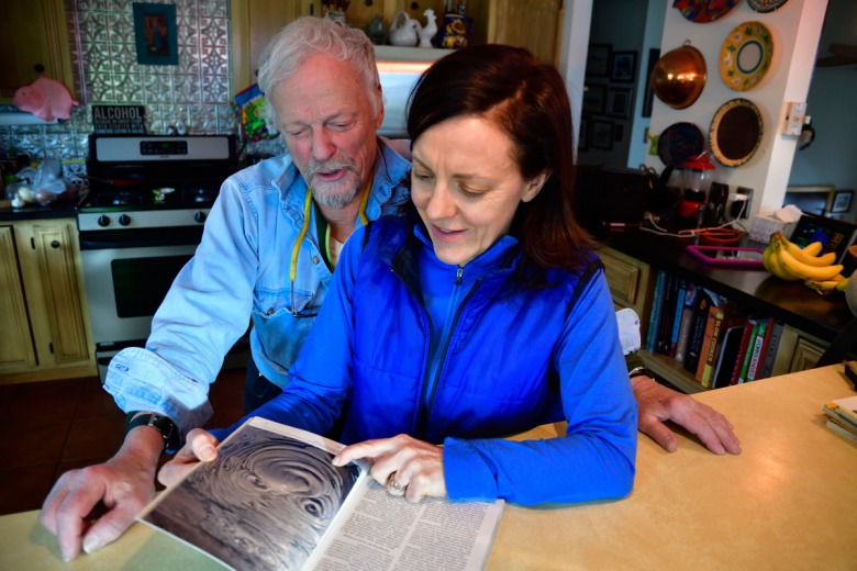 Fuller and his now-grown daughter, Emma, flip through the pages of National Geographic's 1978 issue in which Fuller chronicled his family's life in Yellowstone and his adventures as winterkeeper.  Photo by Joe Sawyer