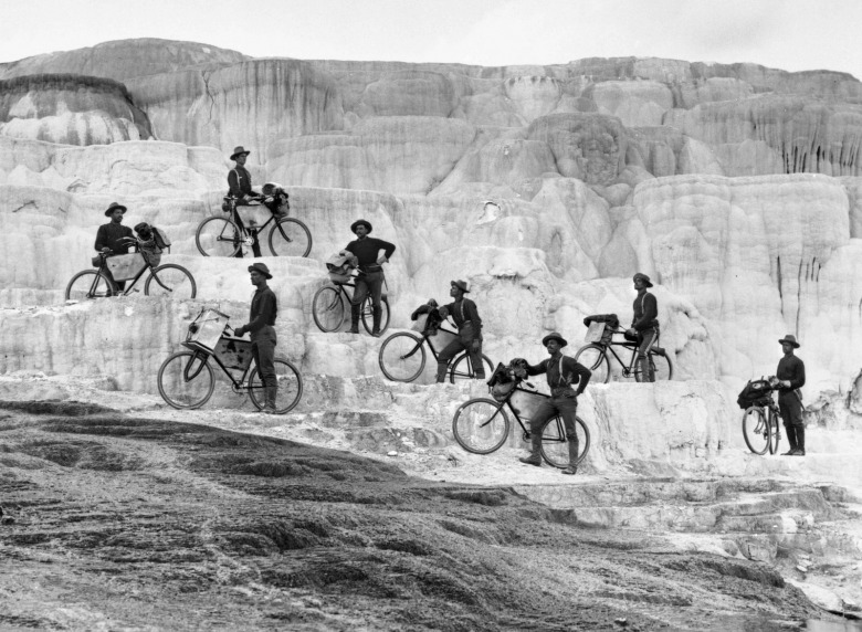 Members of a cavalry unit known as the Buffalo Soldiers ride their frontier bicycles onto the fragile travertine at Minerva Terrace in Yellowstone.