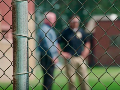Corrections officials chat behind the fence at Pine Hills.
