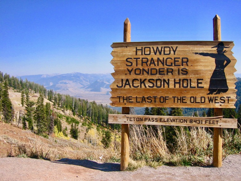 "The old sign that greeted travelers coming over Teton Pass from Idaho on the descent into Jackson Hole. Good or bad, what are the differing characteristics between the ""Old West"" in Greater Yellowstone and the new one?  Photo courtesy Wikimedia Commons"