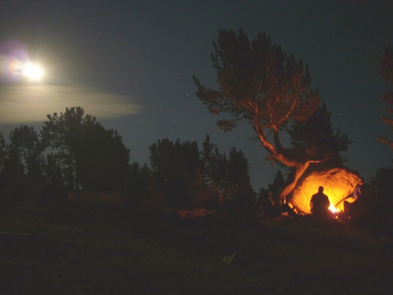 High in the Beartooths above Island Lake, moonlight and firelight illuminate a campsite.  Photo courtesy Jim Hagengruber