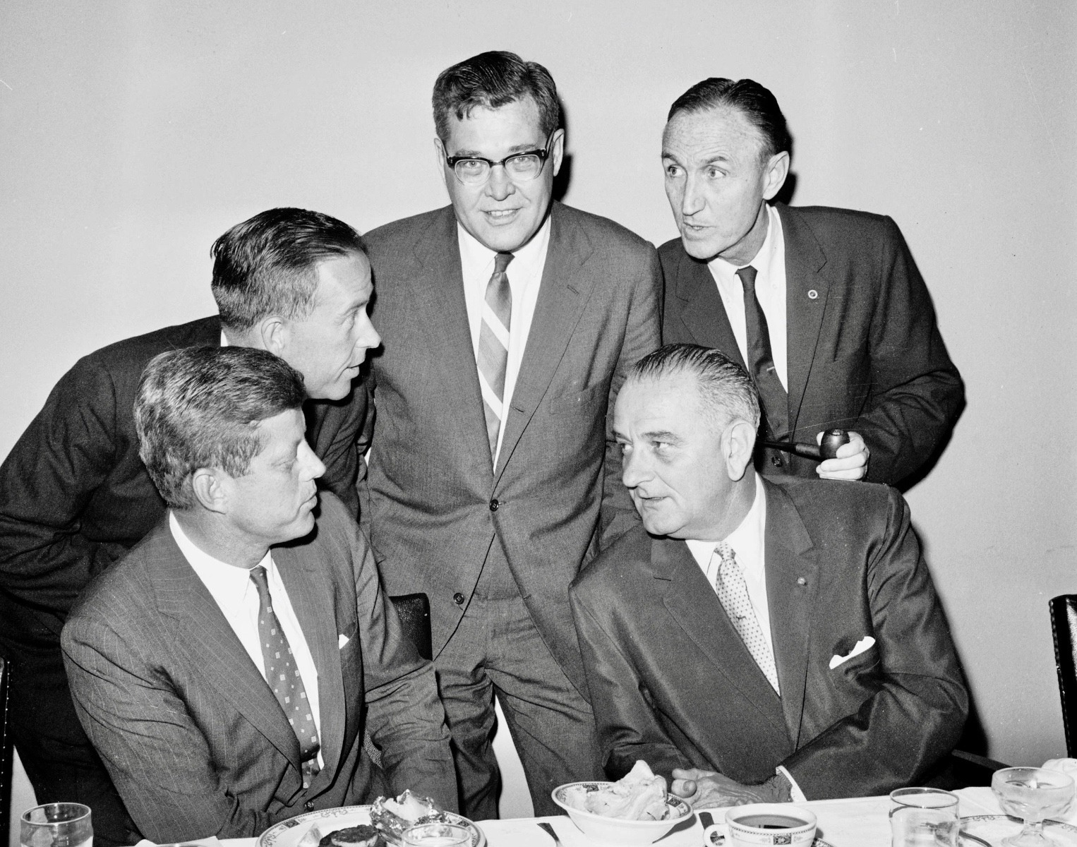 U.S. Rep. Lee Metcalf of Montana (standing, center) meets with Senate Democratic leaders in the U.S. Senate during a meal  in August 1960 prior to the fall 1960 state and national elections. Pictured are (left to right)  1960 Democratic presidential candidate Senator John F. Kennedy; Senator Henry M. Jackson, National  Democratic Party Chairman; Metcalf; Senate Majority Leader Lyndon B. Johnson; and Senate Assistant  Majority Leader Mike Mansfield, August 1960  U.S. Senate Democratic Photograph Studio photograph/courtesy Montana Historical Society