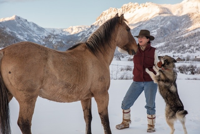 "Julie Anderson visits with an old mustang on the Anderson Ranch in Tom Miner Basin, and her dog, Sage, who was rescued from Alaska.  ""As women, there's another level of maternal connection that occurs—that is where we shine and find safety within ourselves,"" says Julie in reference to horses. Photo by Louise Johns"