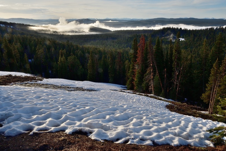 The last remnants of a spring sun-cupped snow cornice overlooks steam plumes rising from geysers and hot springs scattered unto the horizon across the Yellowstone Plateau. In the distance  the Absaroka mountain range rises above the rim of the eastern horizon. Photo courtesy Steven Fuller