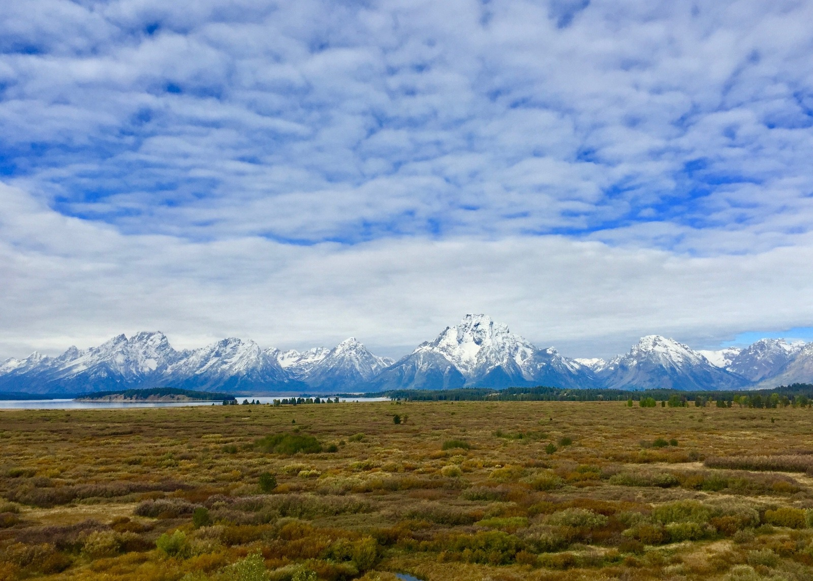 The Tetons from east of Jackson Lake.  Imagine if these flats, today teeming with wildlife and serving a visual sightline to the mountains, were instead covered with a residential subdivision or commercial development all the way almost to the water's edge. While today these lands are treasured as a vital part of Grand Teton National Park's character, some fought against landscape protection.  Photo by Todd Wilkinson