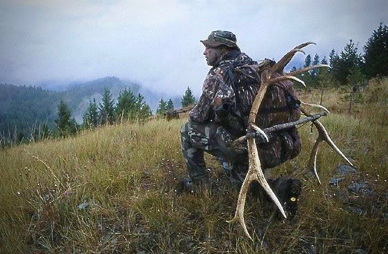 The author out in the backcountry bringing home a pack full of fresh elk meat for the winter and  the antlers of the bull he killed.  Photo by Bob Knoebel.
