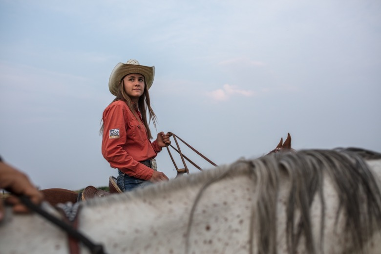 Irene Johnson rides with her sister Sadie as they exercise their horses the evening before their first rodeo of the season. Photo by Louise Johns