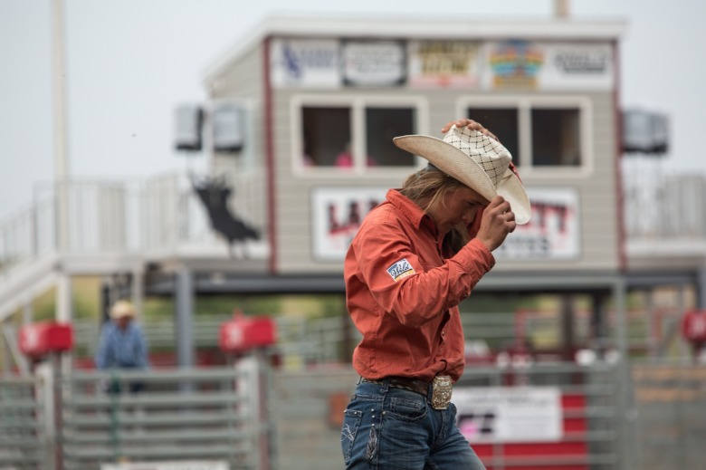 Top: Irene Johnson competes in the goat tying event at the Lewistown Rodeo in August 2018. Since she was 15 years old, Irene has been rodeoing on the Montana High School Rodeo Association. Middle: Johnson competes in the goat tying event at the Lewistown Rodeo in August 2018 then (just above) tucks her hat back on with a sense of accomplishment with horsemanship that is equal parts art and technical skill.  All photos by Louise Johns.
