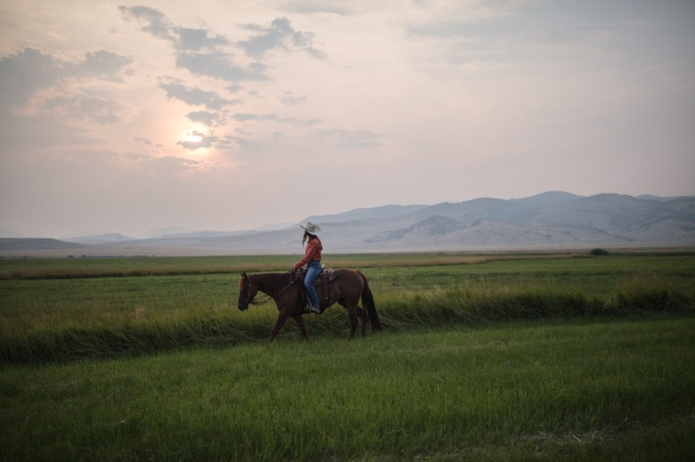 Irene Johnson rides her horse, Perky, on her home ranch under a smokey Montana sky. Photo by Louise Johns
