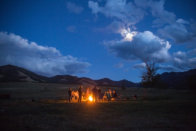 After a day of exploring at the Anderson Ranch, guests partaking in a Common Ground Project outing, gather around a campfire and discuss issues shaping the Greater Yellowstone Ecosystem before climbing into a tipi.  Photo courtesy Louise Johns  (http://www.louisejohnsphoto.com)