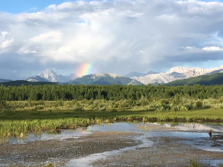 A rainbow highlights the skyline of Horidol Saridag with Delger Khan, the tall peak, towering in the background. This was one of the valleys that served as Watters' carnivore study areas. Photo courtesy Rebecca Watters