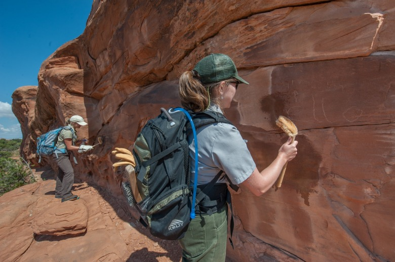 Rangers and volunteers at Arches National Park in Utah remove human graffiti scrawled into the faces of some of the natural archways. Geotagging has led to a lot more people visiting more remote sites without much of a law enforcement presence and with increased people has come vandalism. Photo courtesy Arches National Park.