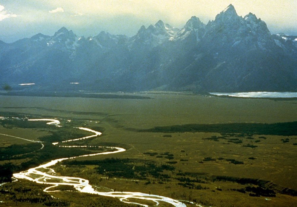 The river known as Ki-moo-e-nim and Yam-pah-pa to the Shoshone tribe, cuts a serpentine course through Jackson Hole beneath the Tetons. While white people coming into the country named it the Snake River, the aboriginal name referenced an herb that grows prolifically along its banks. Photo courtesy Wikipedia