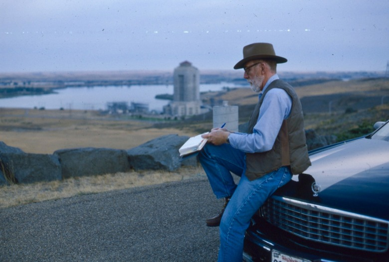 Ivan and Carol Doig spent many seasons traveling across Montana as he compiled new material for books which figured as the backdrop for his stories. Here he is taking notes and making observations at Fort Peck, created by the Missouri River in northeastern Montana. Photo courtesy Carol Doig/MSU Library Doig Archives