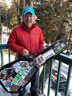 Koehler with a guitar case covered with many of his conservation bumper stickers.