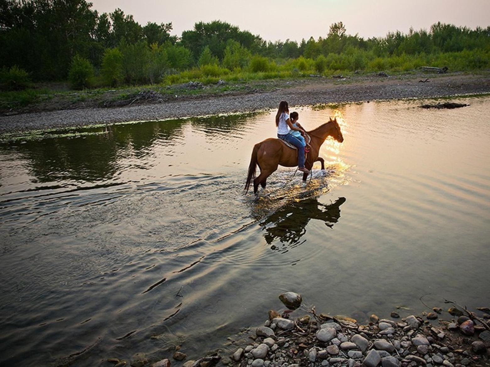 Kendall Edmo takes her daughter on a horseback ride through Blackfeet country in northern Montana. Photo courtesy Rebecca Drobis (rebeccadrobis.com)