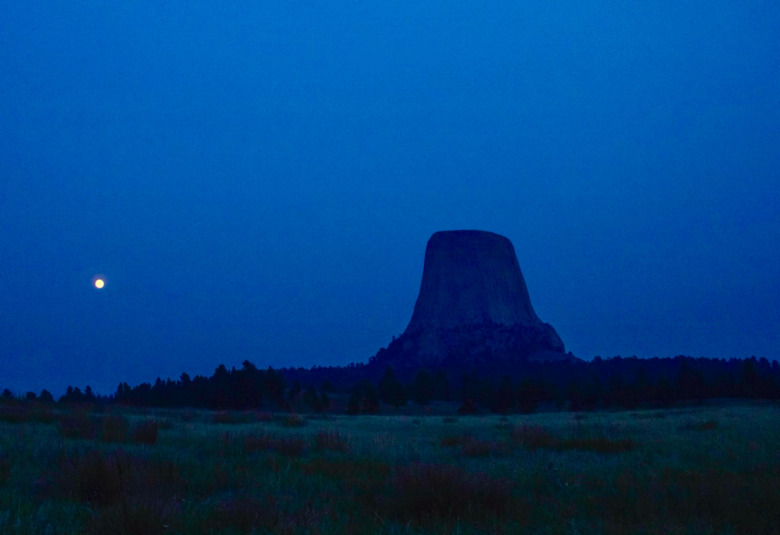 A full moon begins its rise toward to the flat-topped pinnacle of Devils Tower (Bear Lodge). A number of indigenous tribes not only treated Bear Lodge as a holy destination but together with charting the stars navigated their way around the high plains according to the seasons. Photo courtesy National Park Service