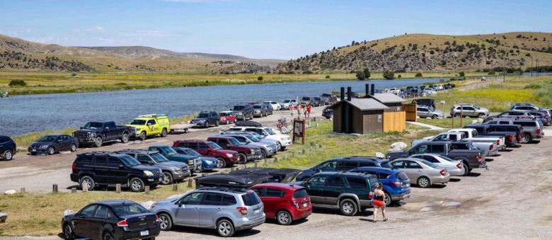This is actually the scene of a slow day at a take-out when tubers upstream took to the Madison River west of Bozeman this summer. Whereas this middle stretch attracts thousands upon thousands of floaters on inflatables and stand up paddle boards, the Upper Madison is dealing with its own issues, involving conflict between recreational anglers, commercial operators and others who say heavy fishing pressure and hooking mortality, along with hot summers bringing lower flows and warmer water, is certain to, at some point, negatively impact the wild, naturally-reproducing trout fishery. Photo by Todd Wilkinson