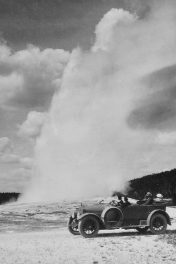 Early auto visitors drive literally up to the cone of Old Faithful Geyser across fragile geothermal crust. Photographer unknown/courtesy NPS