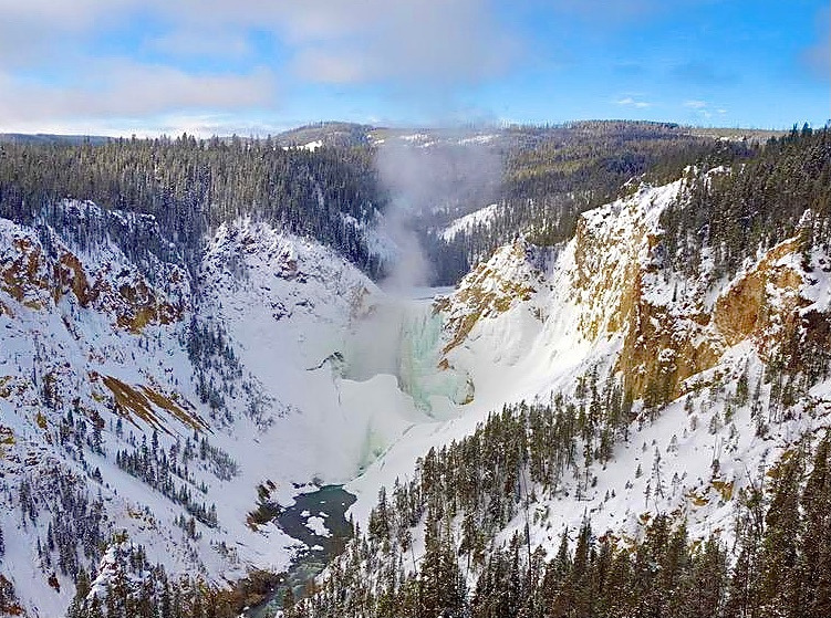 The mighty Grand Canyon of the Yellowstone and its signature focal point, the Lower Falls, has been left to a more muted roar in the aftermath of several days in which the mercury reading remained well below zero. The waterfall is seen in a pastel green sheath, with mist rising as flows from the Yellowstone River tumble into the cold, cold air, turning mist into ice crystals.