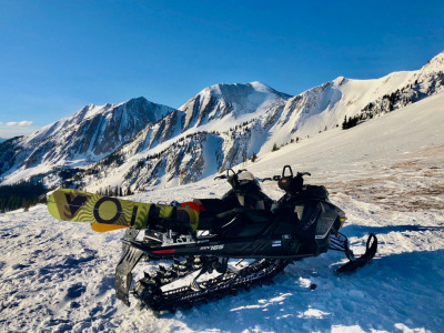 A pair of snowmobiles that carried snowboarders into the backcountry