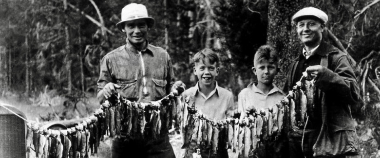 A band of fishing folk, young and old,  pose with their catch in Yellowstone decades before the park imposed strict catch and release regulations. Photo courtesy NPS